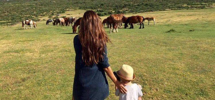 Sara Carbonero con su hijo Martín viendo unos caballos en Navalacruz