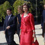 Look de la reina Sofía con vestido lady de color rojo, con textura en relieve y broche floral