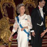 Look de la reina Sofía con vestido de gala largo en color blanco roto y mangas transparentes con detalles florales en relieve