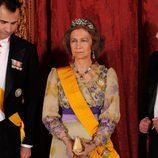 Look de la reina Sofía con vestido de gala largo en color amarillo pastel con llamativos detalles florales en tonos morados y amarillo intenso