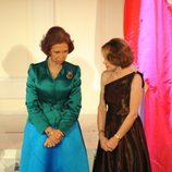 Look de la reina Sofía con vestido de gala largo de tendencia color block combinando falda en azul cian y chaqueta en verde de textura satinada