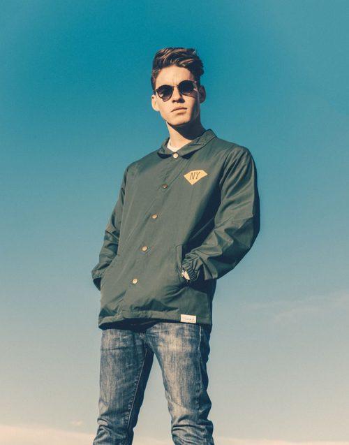 Tyler Clinton posando con una chaqueta para la agencia IMG