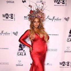 Look elegante premamá de Beyoncé con vestido largo rojo y tocado de flores