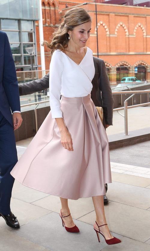La Reina Letizia con top blanco y falda midi en rosa empolvado