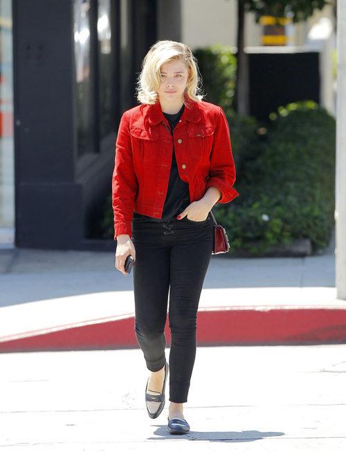 Chloë Grace Moretz con camiseta y jeans negros y cazadora roja
