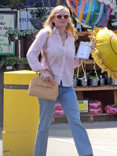 Kirsten Dunts con camisa rosa y pantalones vaqueros anchos