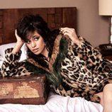 Camila Cabello tumbada sobre la cama con un abrigo de la colección 'Jeans vacaciones 2017' de Guess