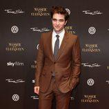 Robert Pattison vistiendo un traje marrón con corbata gris