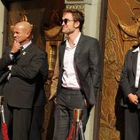 Robert Pattinson luciendo un traje gris oscuro y gafas de aviador