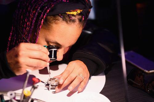 Alicia Keys observando la maquinaria de los relojes Zenith en el evento benéfico en Nueva York