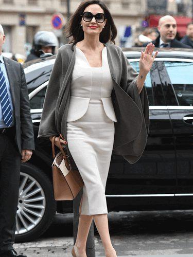 Angelina Jolie con un traje blanco y un bolso marrón