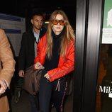 Gigi Hadid con una bomber roja y unos leggings negros saliendo del aeropuerto