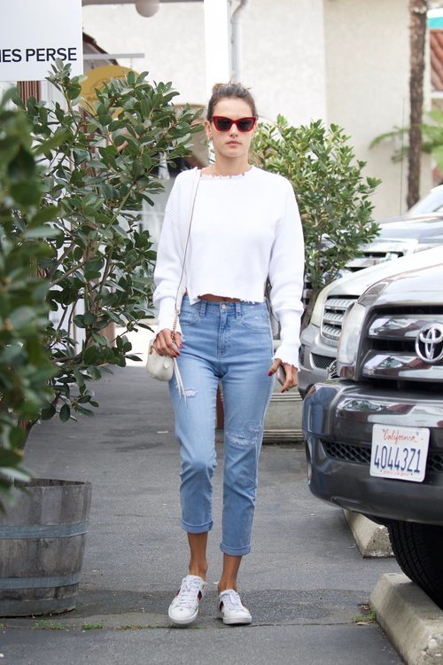 Alessandra Ambrosio con un pantalón vaquero azul claro y un jersey en color blanco paseando por Brentwood 2018
