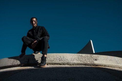 Modelo masculino con un chándal negro de la fimra y las nuevas zapatillas Puma XO 2.0 con The Weekend