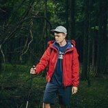 Modelo con un pantalón corto azul y un abrigo rojo de la nueva línea de Outdoor de la nueva colección SS19 de Woolrich
