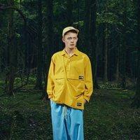 Modelo con un pantalón azul y camisa amarilla de la nueva línea de Outdoor de la nueva colección SS19 de Woolrich