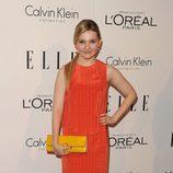 Abigail Breslin con un modelo en naranja y salones beige