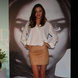 Miranda Kerr con minifalda de cuero beige y camisa blanca