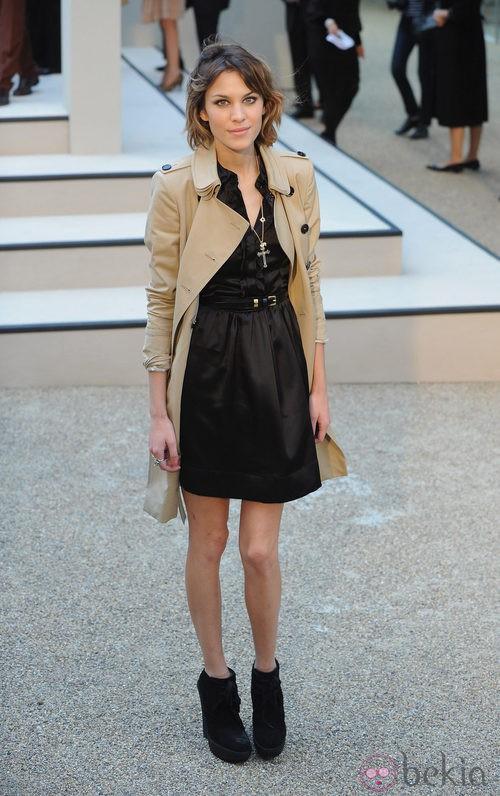Alexa Chung con vestido negro de vuelo y gabardina