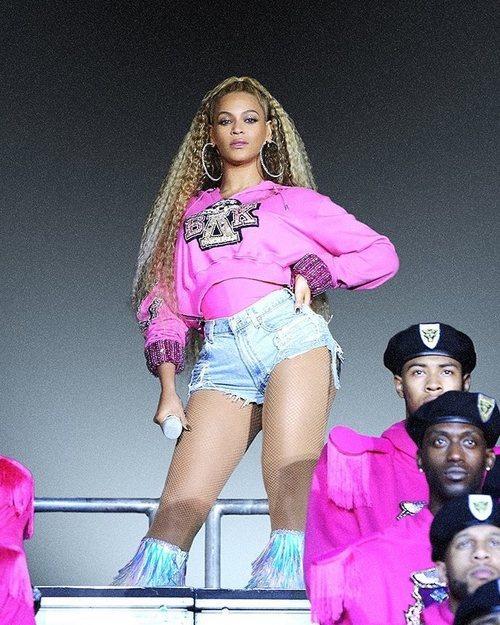 Beyoncé con una sudadera fucsia con capucha de la colección cápsula junto a Balmain 2018