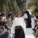 Modelo con una blusa blanca y una falda negra de la colección primavera/verano 2019 de Valentino presentada en Paris Fashion Week