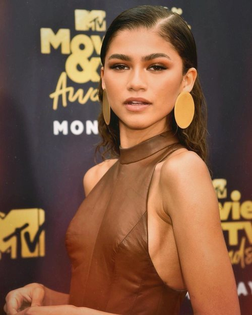 La actriz y cantante Zendaya posando con grandes pendientes dorados