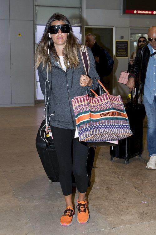 Laura Matamoros en chándal y con una gafas de sol gigantes al llegar al aeropuerto