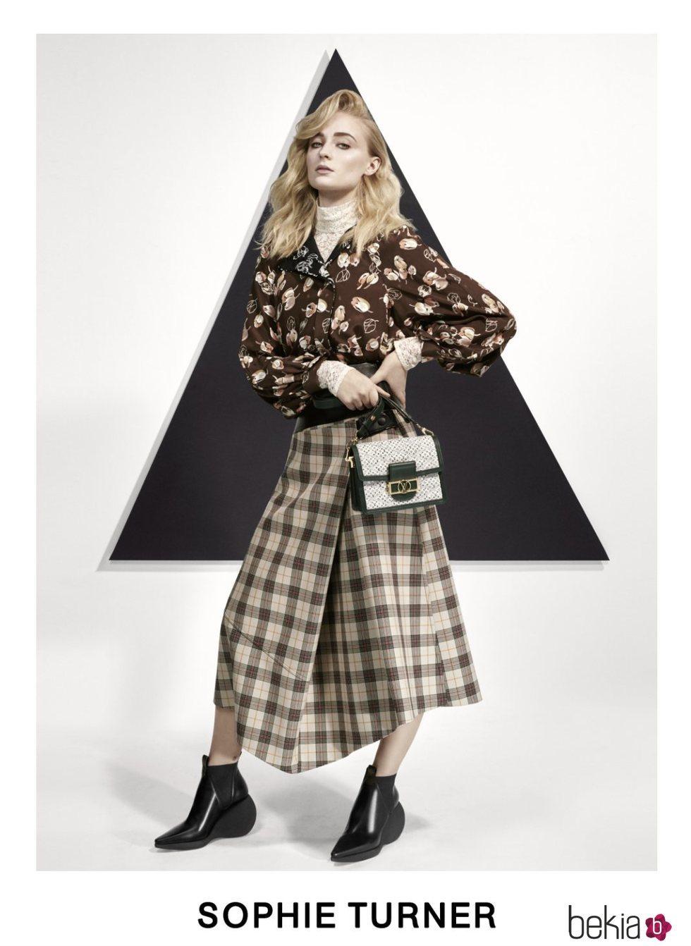 Sophie Turner con una blusa estampada y una falda midi posando para el lookbook Pre-Fall 2019 de Louis Vuitton
