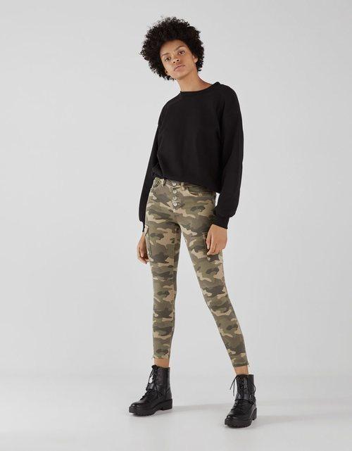 Modelo con unos pantalones con estampado militar de la colección de primavera 2019 de Bershka