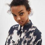 Modelo luciendo una camisa estampada en tonos oscuros de la colección de primavera 2019 de Bershka