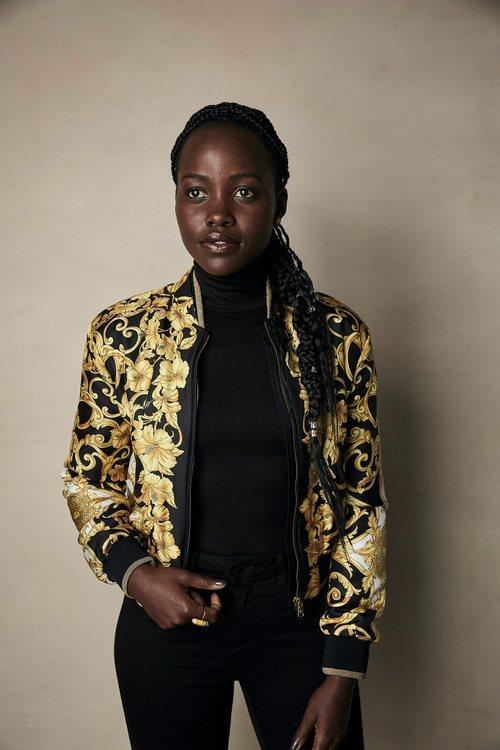 Lupita Nyongo vestida de negro y chaqueta de flores