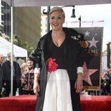 Pink con un vestido bicolor bajo un abrigo largo de mangas abullonadas y un roja en el cinturón recibiendo la estrella en el Paseo de la Fama de Hollywood