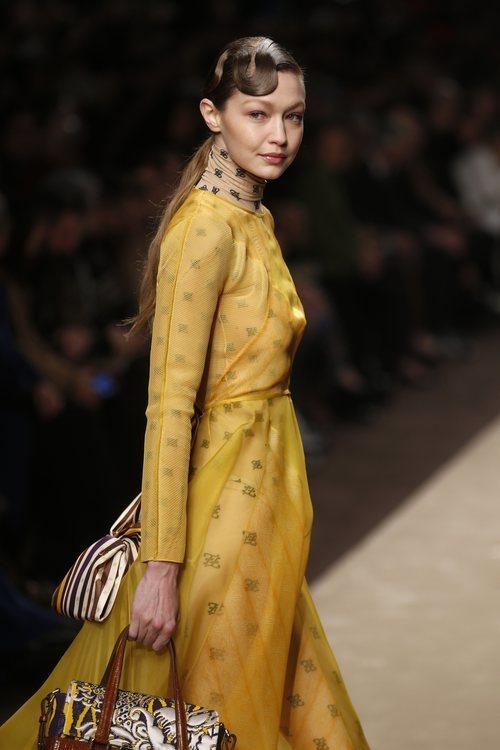 Gigi Hadid con un vestido amarillo superpuesto a un body en el desfile otoño/invierno 2019/2020 de Fendi