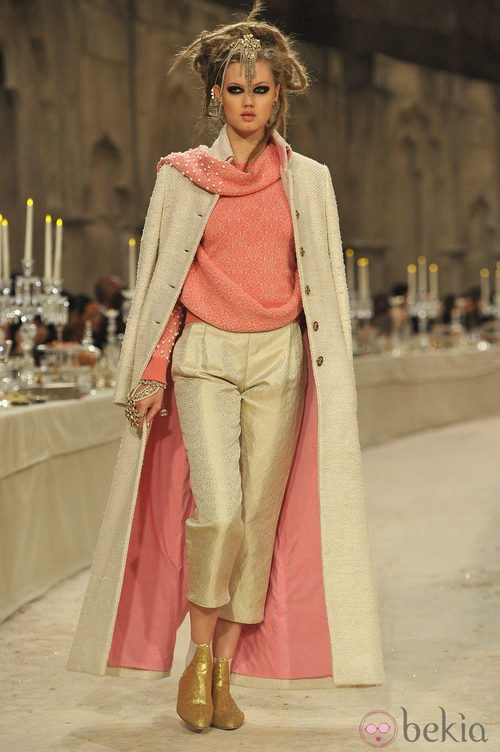 Modelo con jersey salmón, pantalones de lino dorado y abrigo de tweed largo