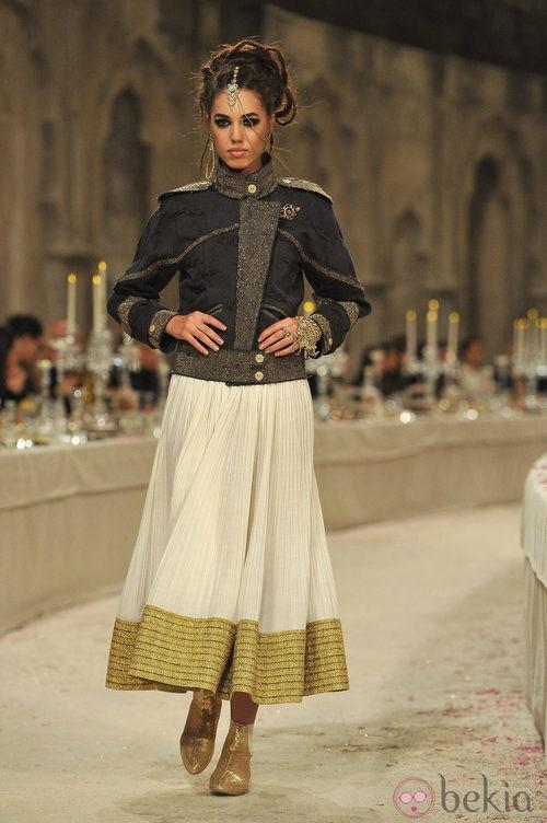 Chaqueta negra con detalles dorados y falda plisada en color hueso y dorado