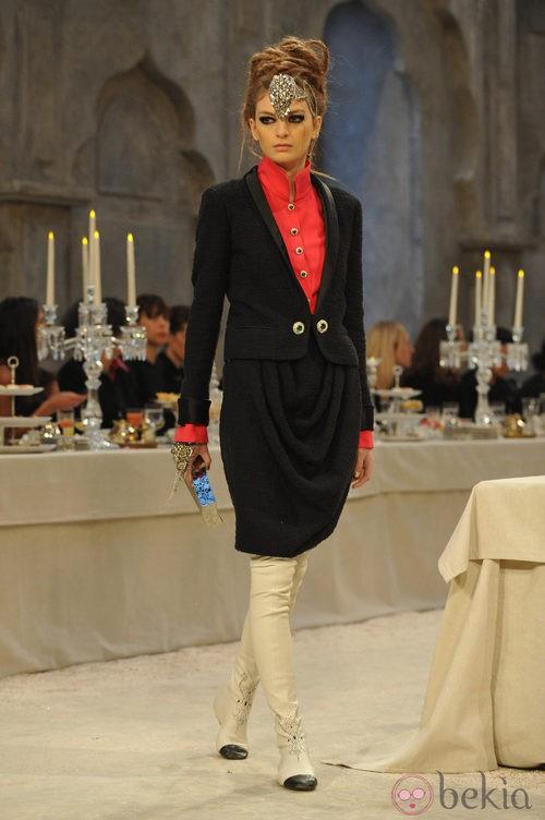 Traje sastre en tweed negro con falda drapeada y botones joya