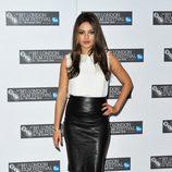 Mila Kunis con falda de cuero negra y camisa blanca