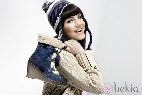 Angy posa con bota tipo trekking y gorro de lana