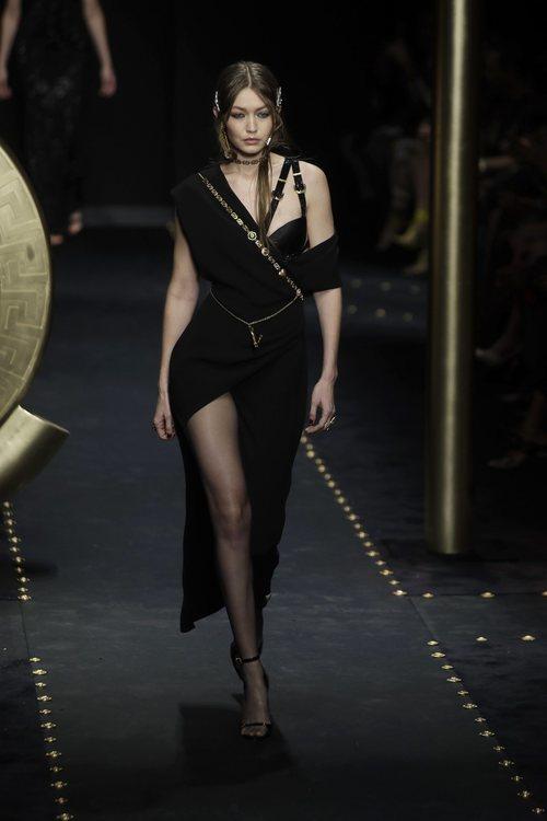 Gigi Hadid desfilando con un vestido asimétrico negro de Moschino otoño/invierno 2019/2020 en la Milán Fashion Week