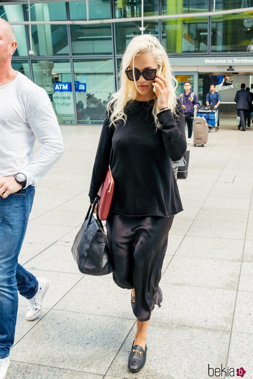 Rita Ora con look 'total black' de vestido satinado en el aeropuerto de Heathrow