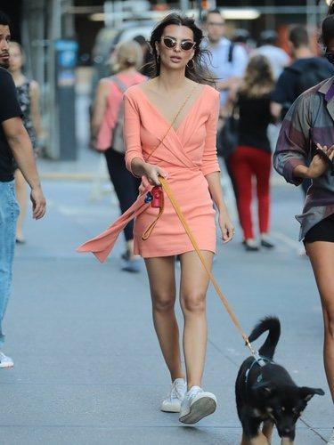 Emily Ratajkowski con minivestido coral paseando a su perro en Nueva York