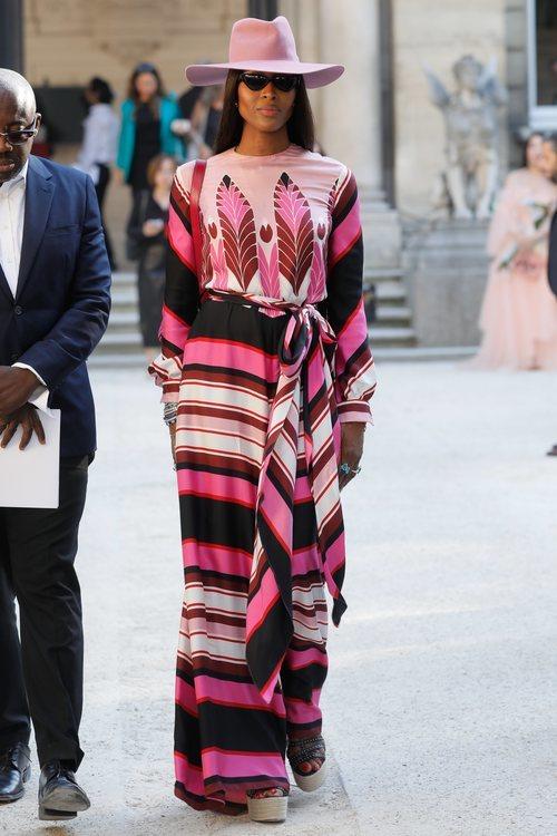 Naomi Campbell con un vestido de estampado asimétrico morado y rosa en la Fashion Week de París