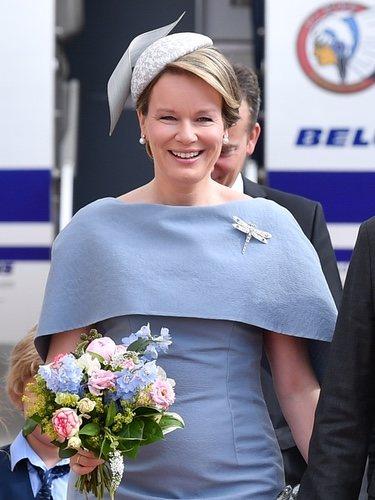 La Reina Matilde de Bélgica con un vestido con capa de color lila aterriza en el aeropuerto de Sajonia