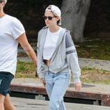 Kristen Stewart con un look sporty chic de lujo con vaqueros lavados rectos y crop top con sudadera de cremallera en Los Ángeles