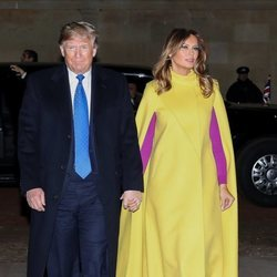Melania Trump con un abrigo capa en amarillo con complementos rosa fucsia en la cumbre de líderes de la OTAN