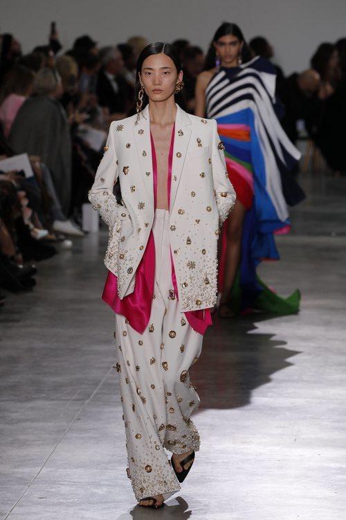 Traje de sastrería oversize en color blanco con incrustaciones de perlas y detalles dorados durante el defile Alta Costura primavera/verano 2020 de Schiapa