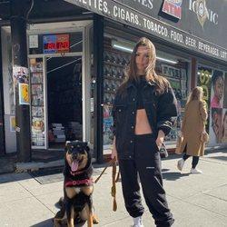 Emily Ratajkowski con un look total black sport paseando a su perro por Nueva York