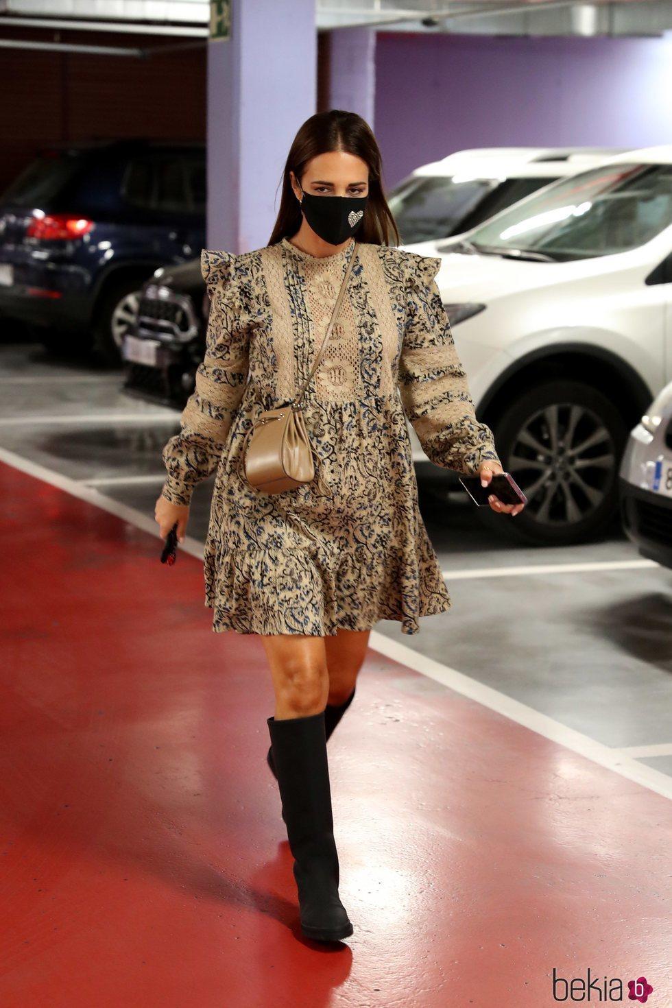 Paula Echevaría luciendo el dúo vestido y botas altas en un parking de Madrid