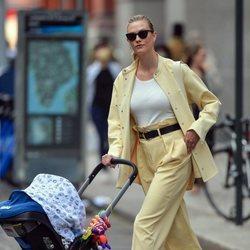 Karlie Kloss con un conjunto amarillo pastel paseando a su hijo por Nueva York