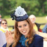 La Princesa Beatriz de York con tocado en azul marino y una gran flor en azul pastel